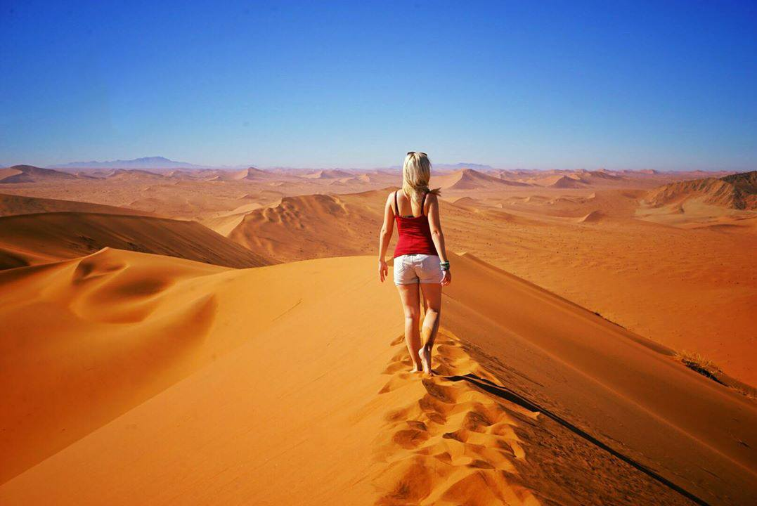 Solo woman traveler on sand dune